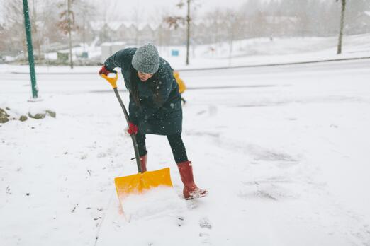 a-woman-shovelling-snow-in-her-driveway-Y7M75T4