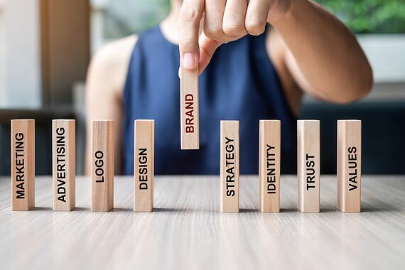businesswoman-hand-placing-or-pulling-wooden-dominoes-with-brand-text-and-marketing-advertising-logo_t20_YwXeLX