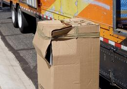 damaged-box-unloaded-from-a-moving-van-cargo-area-56EU78C